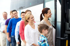 Group of happy passengers boarding travel bus. Transport, tourism, road trip and people concept - group of happy passengers boarding travel bus Royalty Free Stock Images