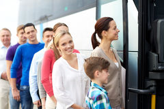 Group of happy passengers boarding travel bus. Transport, tourism, road trip and people concept - group of happy passengers boarding travel bus Royalty Free Stock Photos