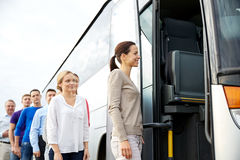 Group of happy passengers boarding travel bus. Transport, tourism, road trip and people concept - group of happy passengers boarding travel bus Stock Images