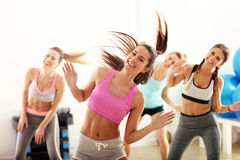 Group of happy people with coach dancing in gym stock image