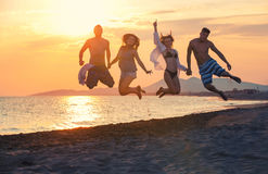 Group of happy people dancing and jumping inside sea on sunset royalty free stock image