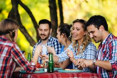 Group of happy people eating food outdoors. Group of happy young people eating food outdoors Royalty Free Stock Photo