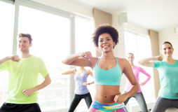 Group of happy people exercising or dancing in gym. Fitness, sport, exercising and training concept - group of smiling people with coach dancing or working out Royalty Free Stock Image