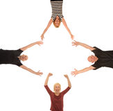 Group of happy people. Group of four happy people with outstretched hands at right angles on a white studio background with copy space royalty free stock photography