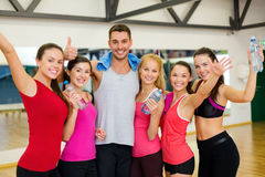 Group of happy people in gym with water bottles. Fitness, sport, training, gym and lifestyle concept - group of happy people in the gym with water bottles and Stock Photo