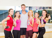 Group of happy people in gym with water bottles. Fitness, sport, training, gym and lifestyle concept - group of happy people in the gym with water bottles and Royalty Free Stock Images
