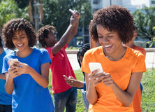Group of happy people with mobile phones. Outdoor in the city in the summer Stock Image