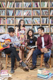 Group of happy people playing music and sing song in library room Stock Images