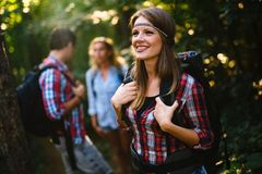 Group of young ahd happy people hiking in forest stock photography