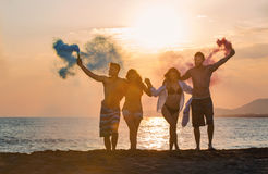 Group of happy people walking on beautiful beach in summer sunset. In their hands is smoke fontain Royalty Free Stock Photos
