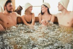 Group of caucasian diverse friends enjoying jacuzzi in hotel spa. Group of happy people young people having great time in spa, relaxing enjoying jacuzzi hot tub royalty free stock photography