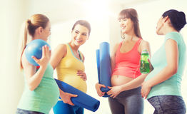 Group of happy pregnant women talking in gym. Pregnancy, sport, fitness, people and healthy lifestyle concept - group of happy pregnant women with sports Royalty Free Stock Photography