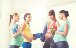 Group of happy pregnant women talking in gym. Pregnancy, sport, fitness, people and healthy lifestyle concept - group of happy pregnant women with sports Royalty Free Stock Photo