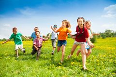 Group of happy running kids. Large group of children running in the dandelion spring field Royalty Free Stock Image