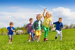 Group of happy running kids with white airplane Royalty Free Stock Images