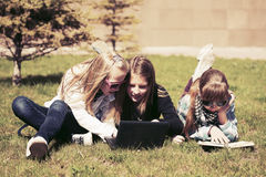 Group of happy school girls lying on a grass in campus. Group of happy teenage school girls lying on a grass in campus Royalty Free Stock Image