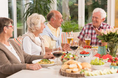 Group of happy seniors eating a dinner. Drinking beer and wine Royalty Free Stock Image