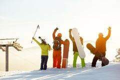 Group of happy skiers and snowboarders having fun. Group of four happy skiers and snowboarders is having fun against sunset backdrop Royalty Free Stock Images