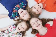 Group of smiling four kids laying on floor. Upper view stock image