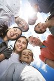 Group of happy smiling friends against blue sky stock images