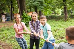 Tug-of-war in park. Group of happy smiling kids playing tug-of-war with rope in green park Royalty Free Stock Photos