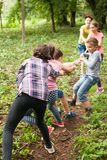 Tug-of-war in park. Group of happy smiling kids playing tug-of-war with rope in green park Royalty Free Stock Images