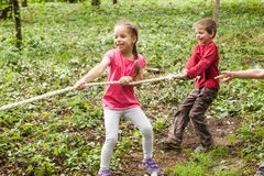 Tug-of-war in park. Group of happy smiling kids playing tug-of-war with rope in green park Stock Images