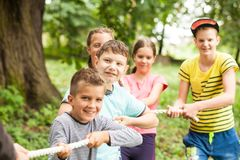 Tug-of-war in park. Group of happy smiling kids playing tug-of-war with rope in green park Royalty Free Stock Photography