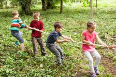 Tug-of-war in park. Group of happy smiling kids playing tug-of-war with rope in green park Royalty Free Stock Photo