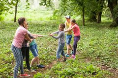 Tug-of-war in park. Group of happy smiling kids playing tug-of-war with rope in green park Stock Image