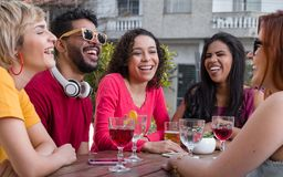 Group of happy smiling people partying together at cafe bar outdoor. Young college students hanging out, having fun at restaurant outside. Group of happy smiling stock photography