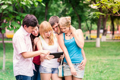 Group of happy smiling Teenage Students. Looking in tablet pc Stock Photo