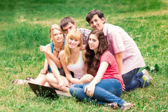 Group of happy smiling Teenage Students Outside College. Looking excited in laptop sitting on a grass Stock Images