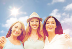 Group of happy smiling women or friends over sky Stock Images