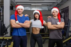 A group of happy sportsmen, in Christmas hats, posing standing and smiling. Indoors in the gym. royalty free stock photography