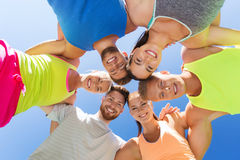 Group of happy sporty friends in circle outdoors Royalty Free Stock Image