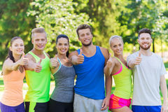 Group of happy sporty friends showing thumbs up Royalty Free Stock Photography