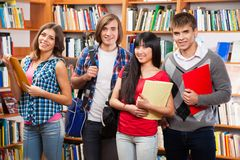Group of happy students. In a library Royalty Free Stock Photo