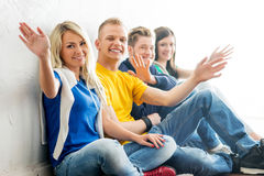 Group of happy students on a break waving. Focus on students. Background is blurry Royalty Free Stock Photo