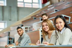 Group of Happy Students  in College. Multi-ethnic group of students sitting at tables in lecture hall of modern college, focus on two beautiful girls looking at Stock Photo