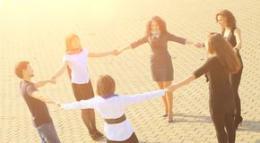 Group of happy students holding hands standing in a circle. Royalty Free Stock Photo
