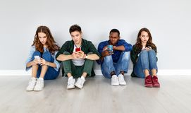 Group of happy students people friends with phones tablets gadgets laugh. A group of happy students people friends with phones tablets gadgets laugh royalty free stock photo