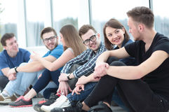 A group of happy students sitting on a window sill and smiling Stock Photo