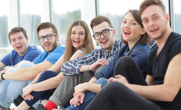 A group of happy students sitting on a window sill and smiling Royalty Free Stock Photography