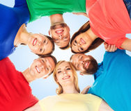 Group of happy students standing together and looking at camera over blue background. School, university, education, concept. stock photography