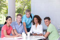 Group of happy students studying. By the table Royalty Free Stock Photo