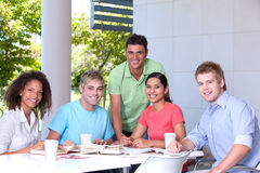 Group of happy students studying. At a table Royalty Free Stock Image