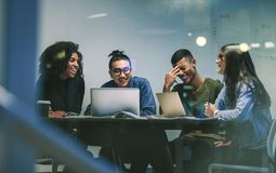 Group of happy students in university library. Group of happy young students in university library sitting at a table with their laptop and smiling. Multi-ethnic stock photography