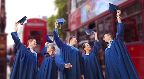 Group of happy students waving mortarboards Royalty Free Stock Photos