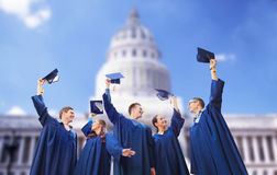 Group of happy students waving mortarboards Stock Image